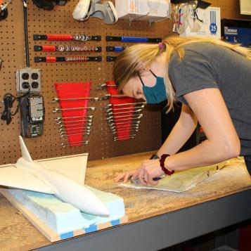 Image of Kali Boyd at a work bench in ARC cutting out a mold with the UAV model beside her